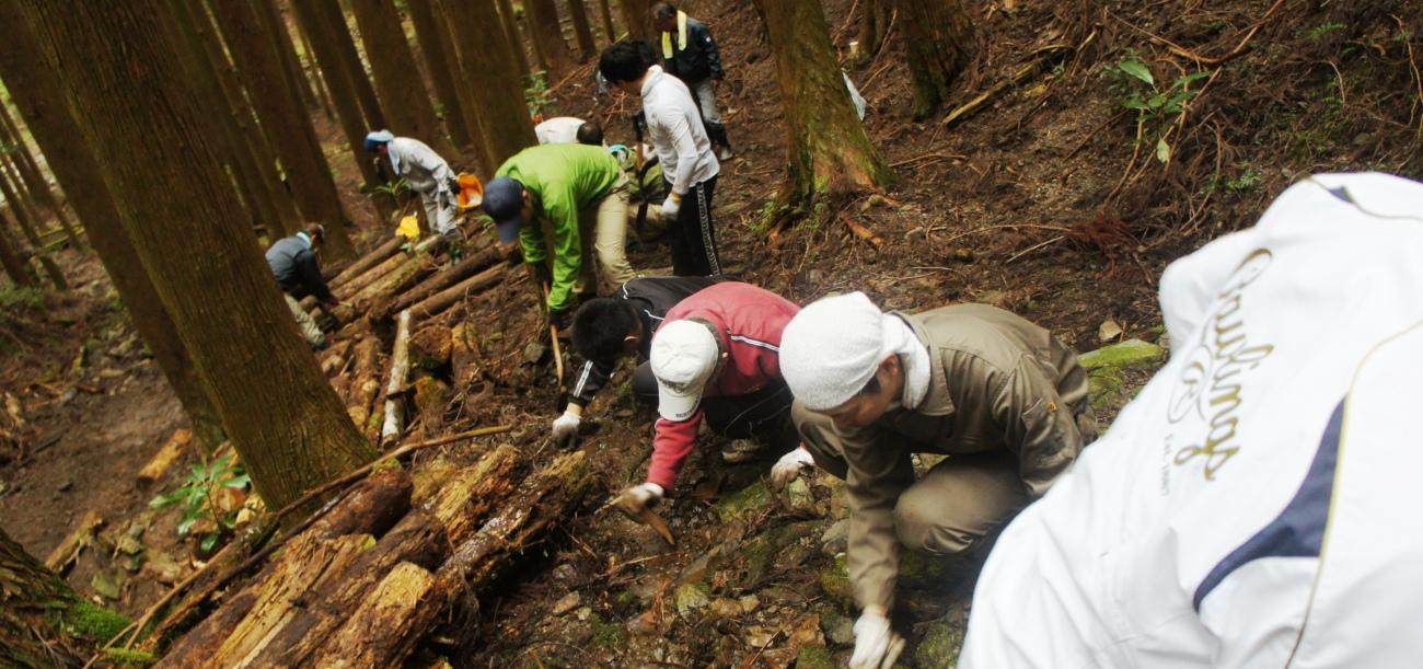 滑り落ちないように注意しながら熊野古道を修繕します